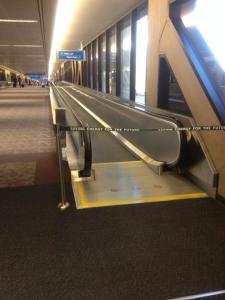 "In this photo taken at the Denver airport, a moving walkway is blocked off with a ribbon barrier, on which appears the text: ""Saving Energy for the Future."" The walkway is on the right, moving toward the next terminal, while on the left, there is dark carpet and a view of the long walk to the next terminal, which spans the length of several more moving walkways."